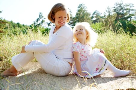Portrait of mother and her daughter sitting on rug outside and looking at each other Stock Photo - 7409401