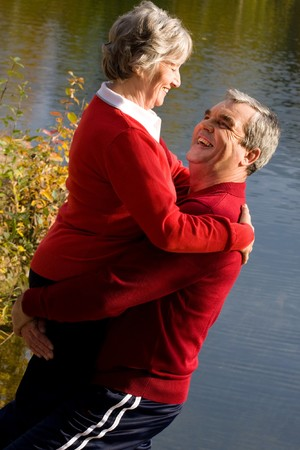 Image of senior man holding his wife while spending time by the lake photo