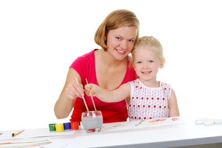 Photo of mother and daughter painting with aquarelle and looking at camera photo