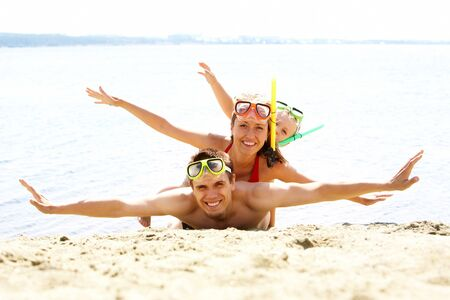 Portrait of cheerful couple and their son in diving equipment lying on sand and looking at camera photo