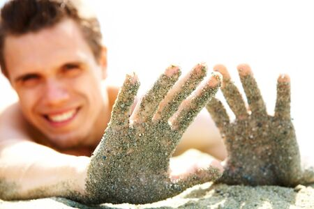 Photo of smiling guy lying on beach and showing his hands covered with sand while sunbathing photo