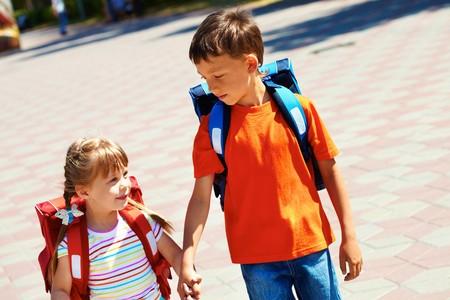 ni�os saliendo de la escuela: Retrato de amigos inteligentes con mochilas caminando por la carretera de la ciudad en d�a soleado