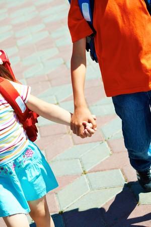 ni�os saliendo de la escuela: Dos amigos con mochilas, ir a la escuela por v�a de la ciudad mientras mantiene con las manos