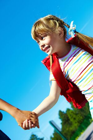 Portrait of smart girl with backpack holding her friend by hand against blue sky photo