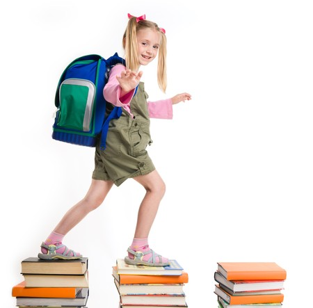 ways to go: Portrait of girl with backpack walking from top to top of book piles