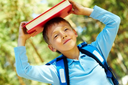 school backpack: Foto de colegial diligente con libro sobre su cabeza al aire libre