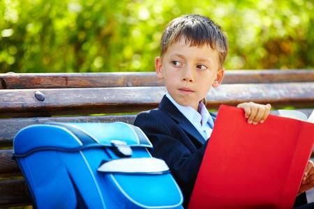 beiseite: Portrait of smart Boy sitting in the Park with interessante Buch und beiseite suchen Lizenzfreie Bilder