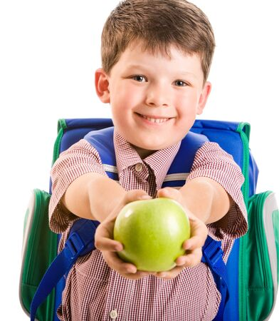 Portrait of cute smiling schoolboy giving a green apple  photo