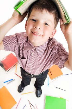 diligente: Ojo de pez disparo de chico diligente con libro sobre su cabeza mientras que hacer deberes