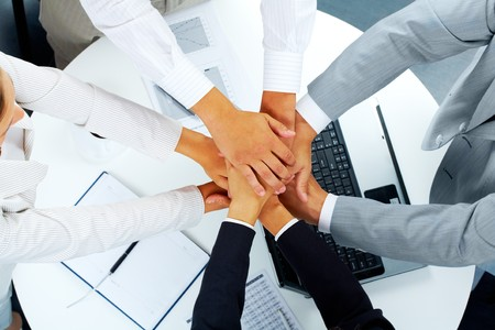 hands joined: Above angle of business partners making pile of hands over workplace   Stock Photo