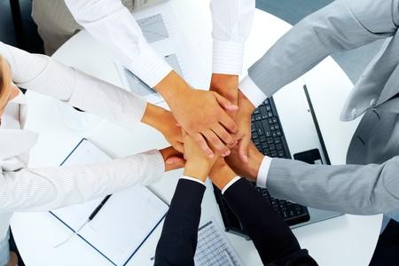 manos unidas: Por encima de �ngulo de asociados de negocios haciendo mont�n de manos sobre el lugar de trabajo