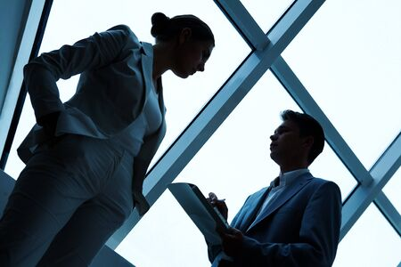interviewing: Two silhouettes of businesspeople interacting with each other in the office