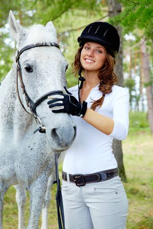 dressage: Image of happy female with purebred horse near by Stock Photo