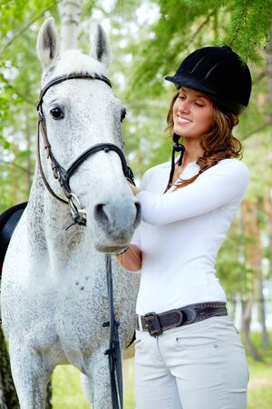 Image of happy female grooming purebred horse outdoors photo