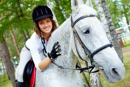 Image of happy female jockey on purebred horse outdoors photo