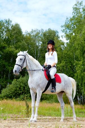 appaloosa: Image of happy female jockey sitting on appaloosa horse outdoors Stock Photo