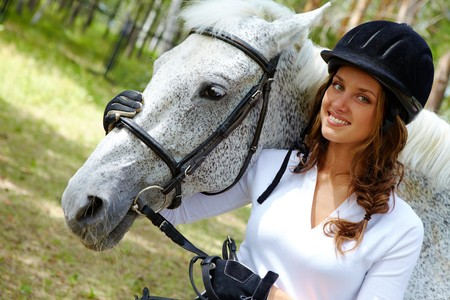 Image of happy female in riding cap embracing purebred horse and looking at camera photo
