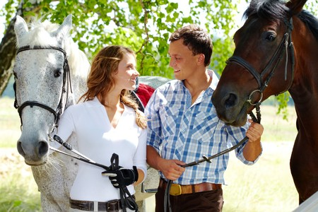 Image of happy couple with purebred horses looking at each other photo