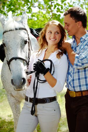 Image of happy woman between purebred horse and her sweetheart outside photo