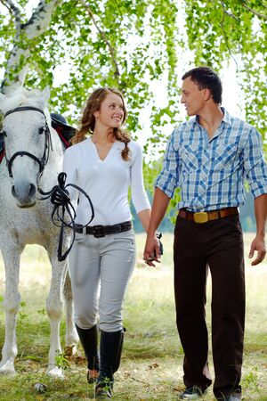 Image of happy woman surrounded by purebred horse and her sweetheart during walk photo