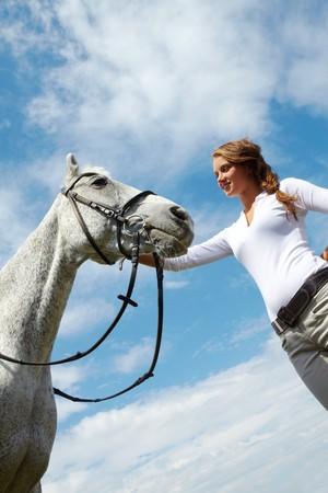 Bild von glücklich weiblichen grooming reinrassige Pferde gegen bewölkten Himmel  Standard-Bild