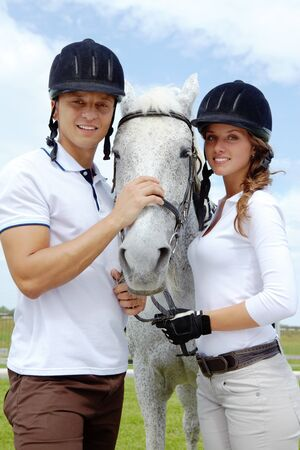 Image of happy couple with purebred horse looking at camera photo