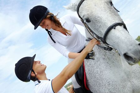 appaloosa: Image of handsome man helping woman to sit on purebred horse Stock Photo