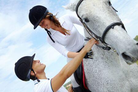 jockey: Imagen de hombre guapo, ayudando a la mujer a sentarse en el caballo de pura raza