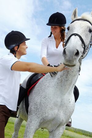 Image of handsome man giving instructions to woman sitting on purebred horse photo