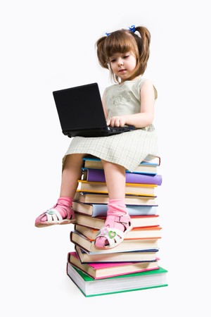 Image of preschooler sitting on the heap of books and working with laptop photo