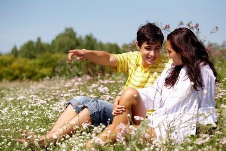 boyfriend: Retrato de hombre joven mostrando algo a la mujer al aire libre