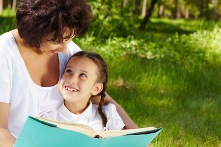 girl reading book: Portrait of curious girl looking at her mother while discussing book in park Stock Photo