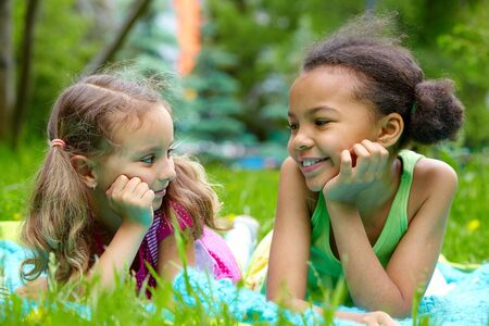 Portrait of two cute girls having rest and looking at one another on summer day Stock Photo - 7463769