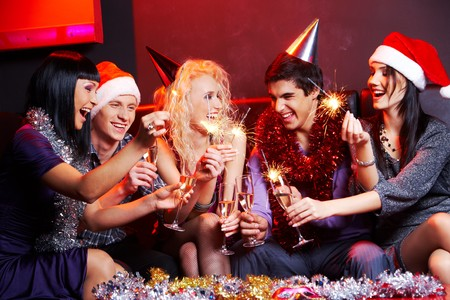 party friends: Portrait of laughing friends enjoying xmas lights at new year party Stock Photo