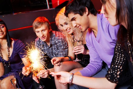 trumpery: Group of friends looking at sparkling Bengal lights during party