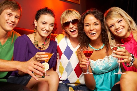 Portrait of young people with martini glasses laughing in the nightclub photo