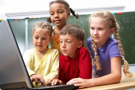 Portrait of smart schoolgirls and schoolboy looking at the laptop with blackboard on background  photo