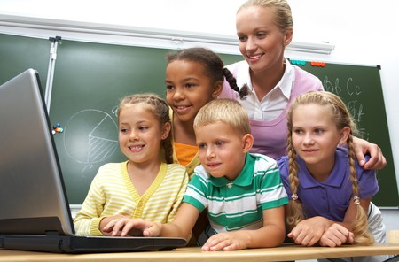 Portrait of pupils looking at the laptop with teacher near by Stock Photo - 7484425
