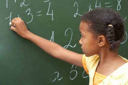 sums: Portrait of smart schoolchild standing at blackboard and doing sums Stock Photo