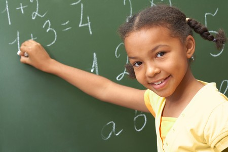 learning by doing: Portrait of smart schoolchild standing at blackboard and looking at camera