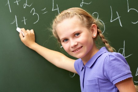 Portrait of smart schoolchild by the blackboard looking at camera photo