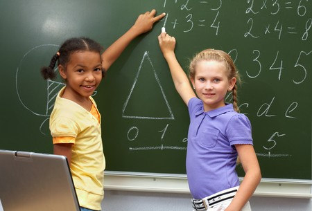 Portrait of smart schoolgirls by the blackboard pointing at it and looking at camera