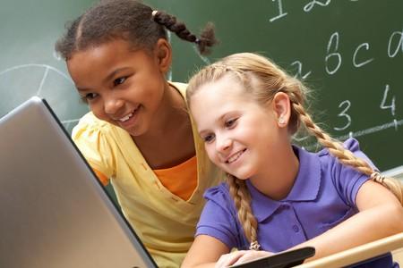 salle de classe: Portrait de deux �coli�res en regardant le portable au cours de la le�on