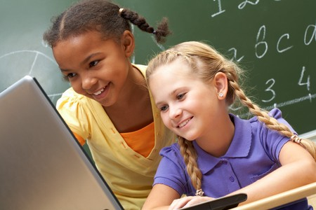 education technology: Portrait of two schoolgirls looking at the laptop during lesson