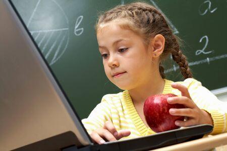 ni�o empujando: Retrato de colegiala pretty mirando la laptop atentamente