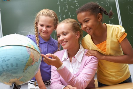 Portrait of pupils looking at globe being pointed at by lecturer during lesson photo