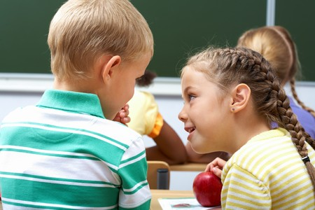 children talking: Portrait of schoolchildren sitting in classroom and chatting at lesson
