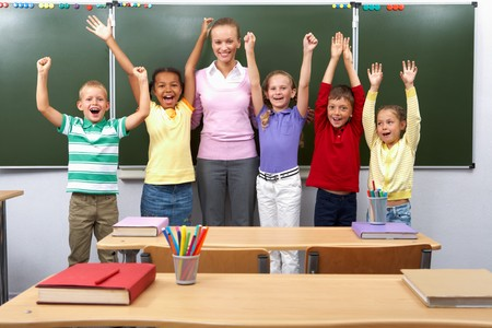 Line of cute schoolchildren raising arms with their teacher in the middle  Stock Photo - 7484418