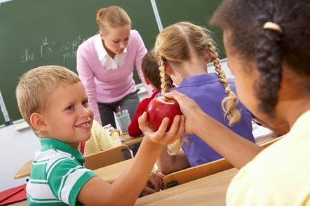 discutere: Ritratto di scolara passando mela rossa al compagno durante la lezione Archivio Fotografico