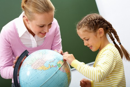 Portrait of cute girl and teacher looking at globe during lesson photo